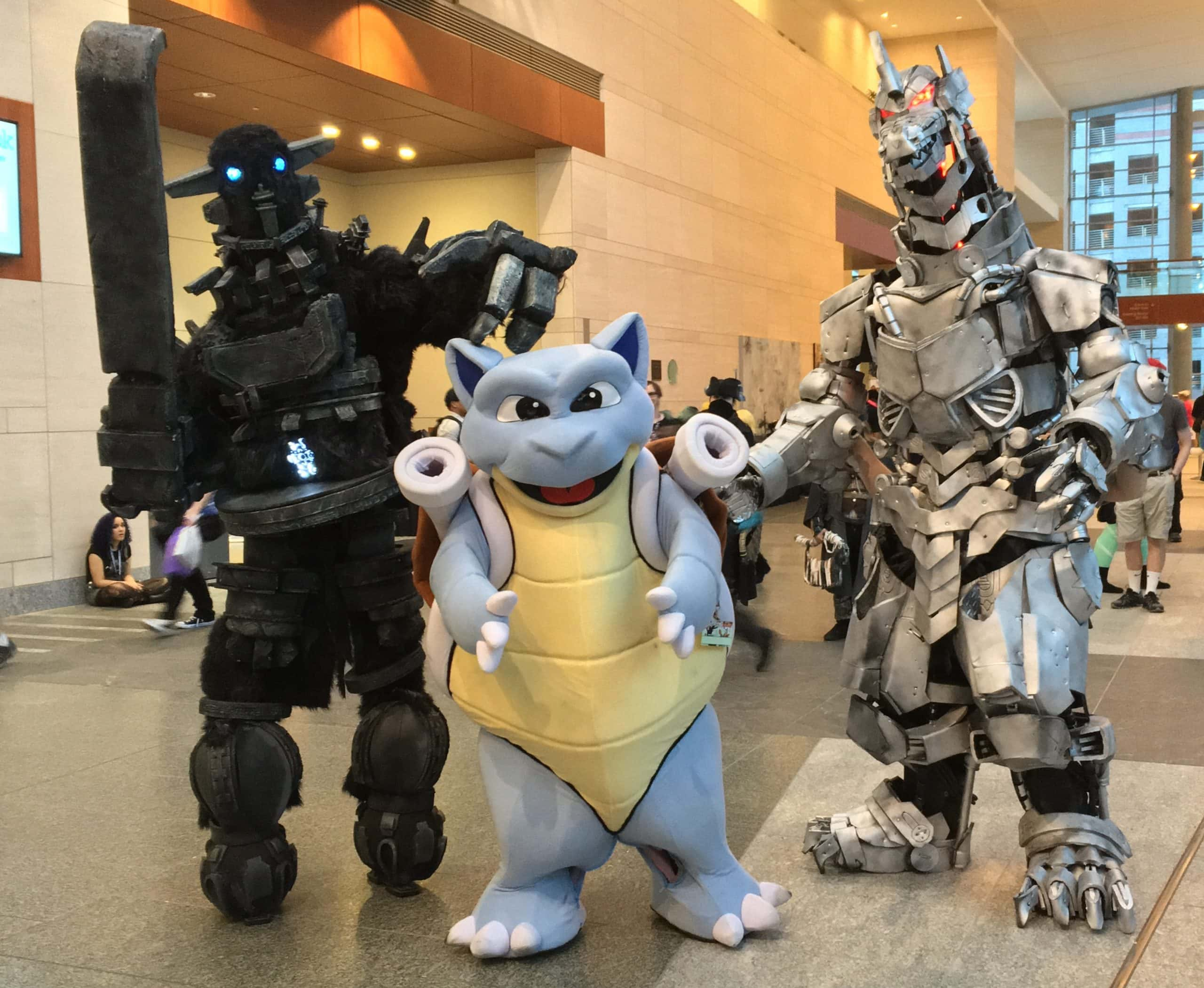 People cosplaying Blastoise, Mechagodzilla, and Gaius in the Raleigh Convention Center on a gray tile floor.